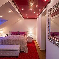 Schlafzimmerdecke mit roter Lackspanndecke und Sternenhimmel